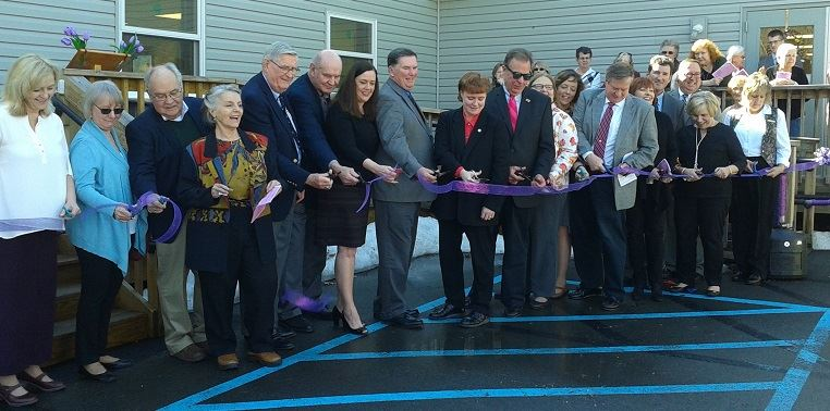 State and county officials line up for the ribbon cutting at the Adult Day Services facility at the