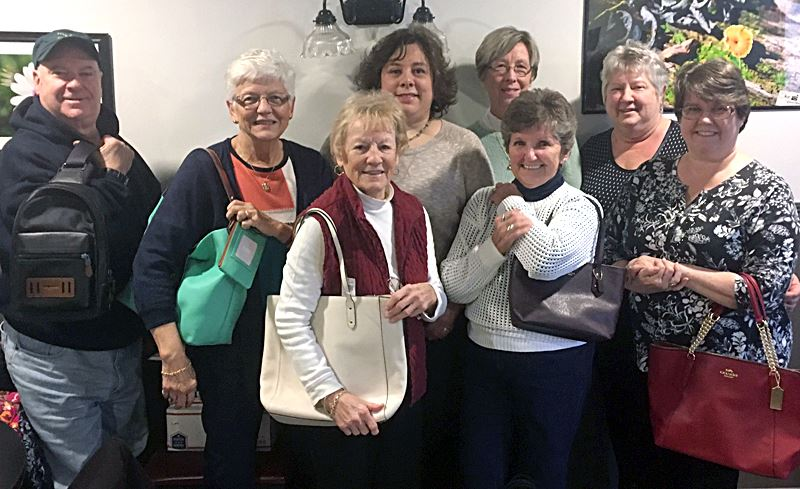 Auxiliary Committee members showing off designer handbags for Bingo Night.