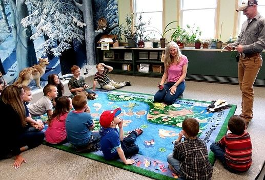 Young children gather to learn about forest animals.