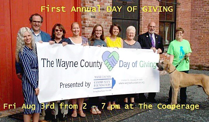 Representatives from some of the non-profit groups pose behind the Day of Giving.