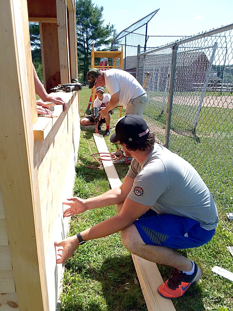 Wayne Highlands Tech Ed teachers and student nail siding to new home dugout at County Farm.