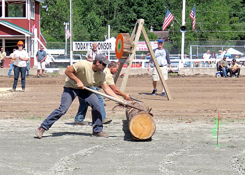 Two lumberjacks use cant hooks to roll a log toward the pins at the Woodsmen's Competition.
