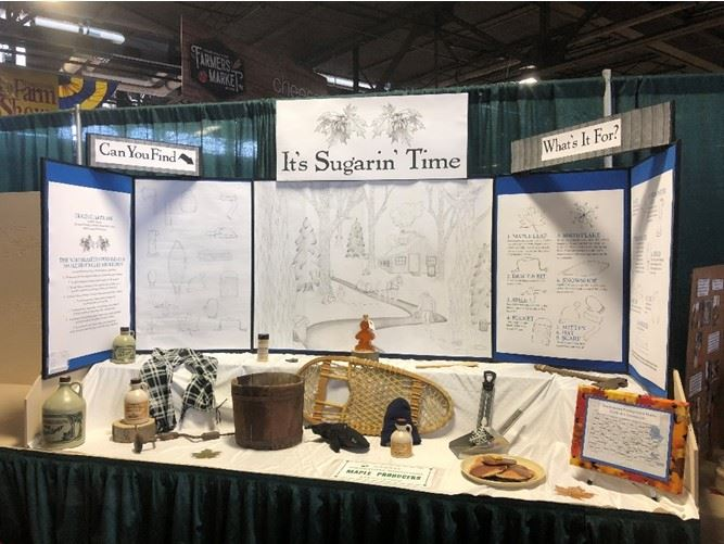 A exhibit table containing maple sugaring equipment and products.