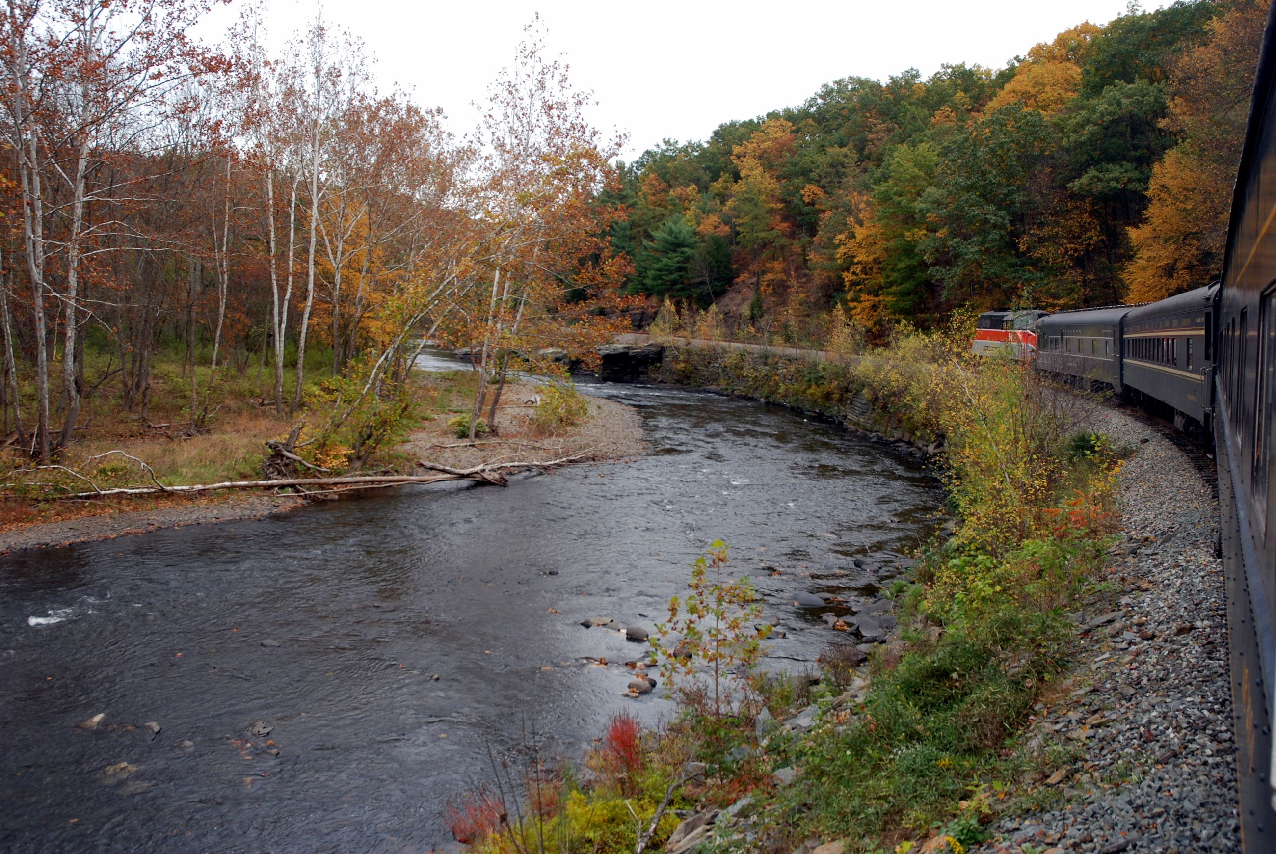 An image of the Lackwaxen River and the Stourbridge Line train cars trailing around a bend.