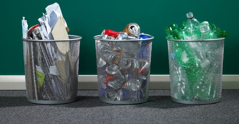 An image of three wire waste baskets holding separate paper, plastic and glass recyclables.