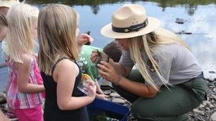 Female National Park Service Ranger show two young girls aquatic specimens.