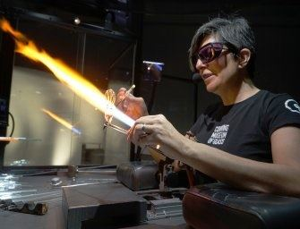 A woman demonstrates the technique of working a glass sculpture using fire at the Corning Museum of
