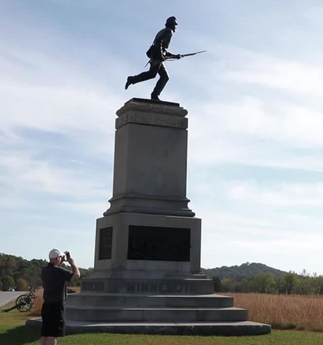 A man taking a picture of a monument on the Gettysburg Battlefield.