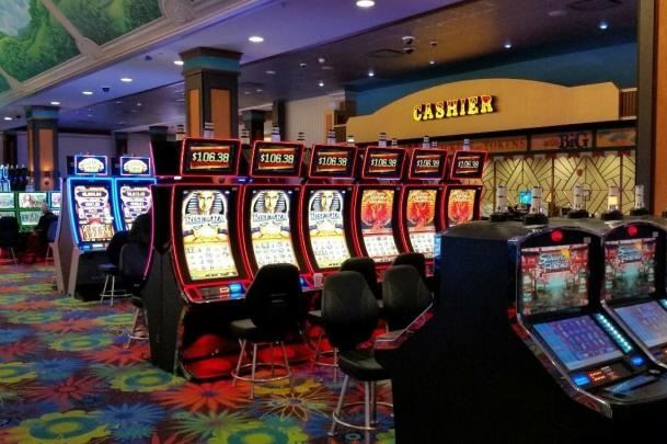 An image of several rows of slot machines with a cashier window in the background.